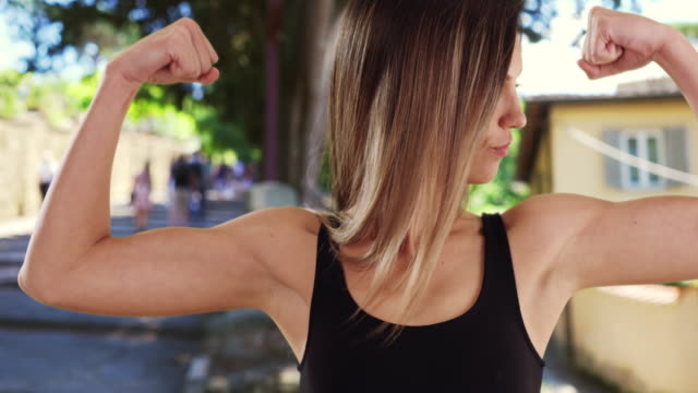 fit caucasian girl in her 20s showing off arm muscles outside while in italy - bicep stock videos & royalty-free footage