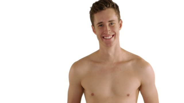 fit caucasian male at the beach smiles at camera on white background - 水泳パンツ点の映像素材/bロール