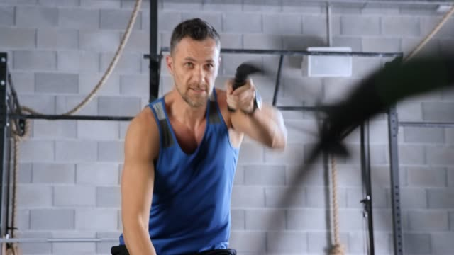 fit caucasian man doing a battle rope exercise in the fitness center - quarantenne video stock e b–roll