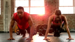 Fit couple doing push ups together in gym