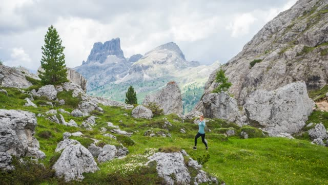 Fit female runner running off the beaten path on a grassy meadow, surrounded by mountains