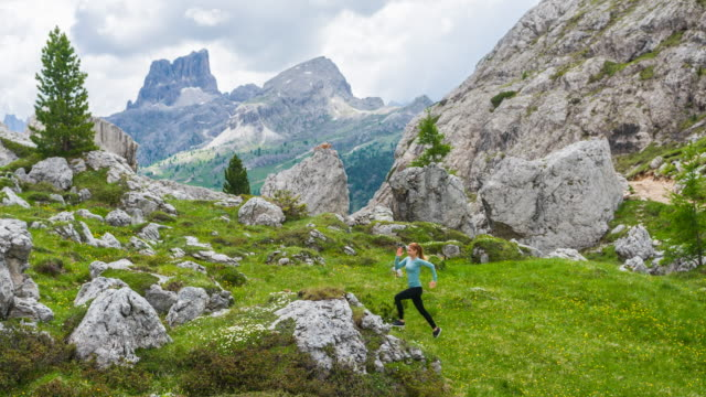 fit female runner running off the beaten path on a grassy meadow, surrounded by mountains - off the beaten path stock videos & royalty-free footage