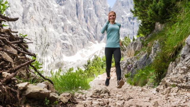 Fit weibliche Läufer läuft über felsige Pfade in alpinem Gelände