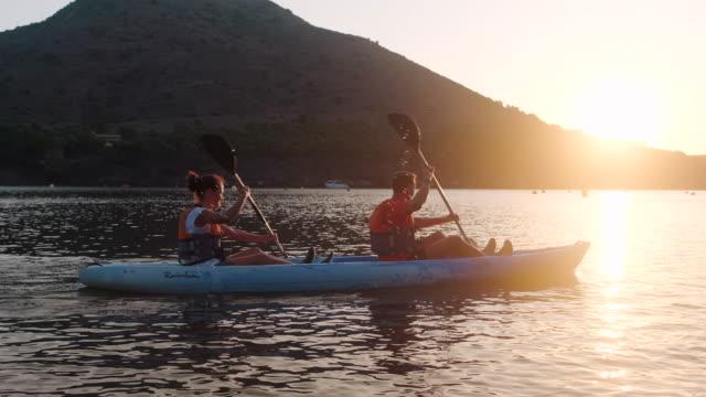 vídeos de stock e filmes b-roll de fit friends paddling kayak off the costa brava at dawn - kayaking