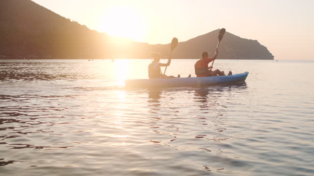 fit friends paddling kayak off the costa brava at dawn - using a paddle stock videos & royalty-free footage