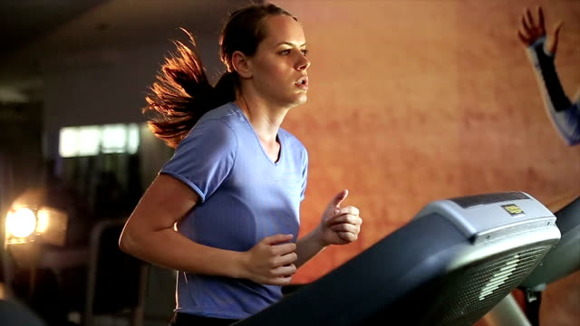 Fit Girl Doing Cardiovascular Exercising On Treadmill