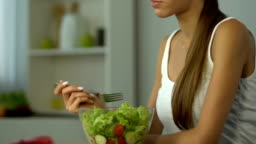 Fit girl eating salad instead of pie, low-carb diet, vitamins, healthy lifestyle