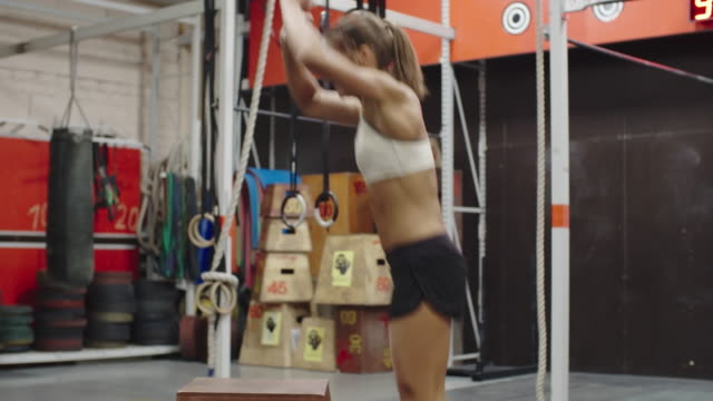 Fit girl practicing box jumps