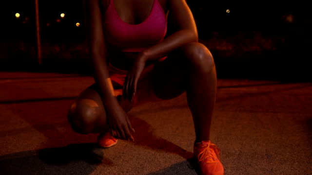 fit girl training at night - crouching stock videos & royalty-free footage