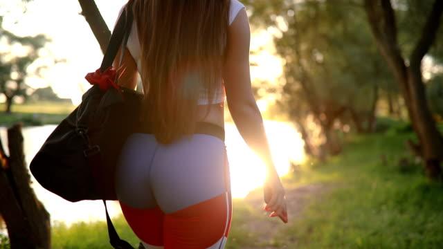 vidéos et rushes de fille marche au bord de la rivière après la formation - vêtement de sport