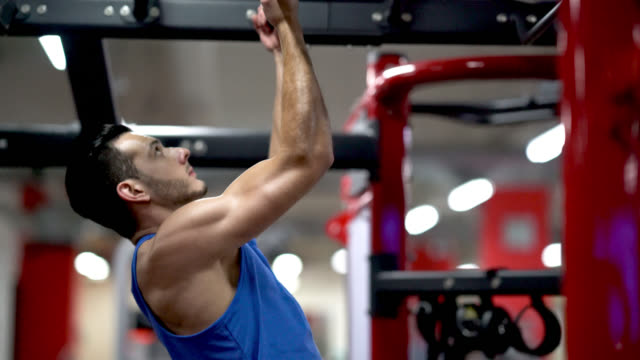 fit guy at the gym doing pull ups - chin ups stock videos and b-roll footage