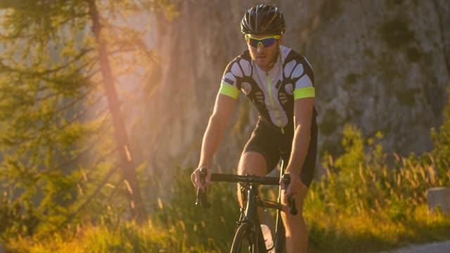 美しい晴れた夏の日に、男性アスリートライディングロード自転車にフィット - アウトドア点の映像素材/bロール