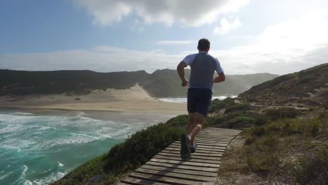 vidéos et rushes de forme mâle longe un sentier côtier - allée couverte de planches