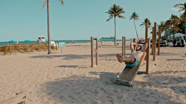 vidéos et rushes de ms fit homme faisant des ascenseurs de jambe sur la plage ensoleillée, miami beach, miami, floride, etats-unis - miami