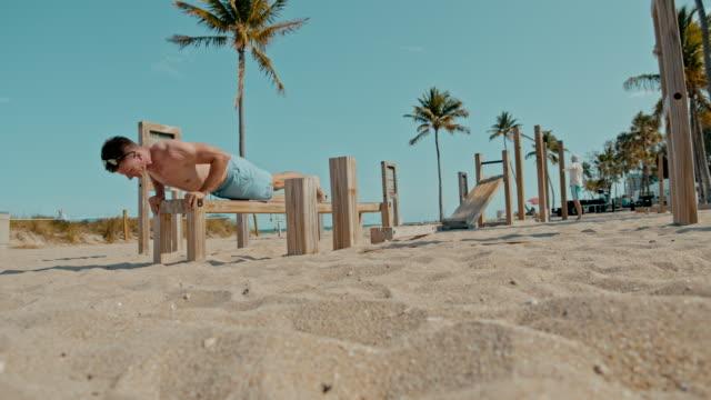vidéos et rushes de ms fit homme faisant des pompes sur la plage ensoleillée, miami beach, floride, etats-unis - miami