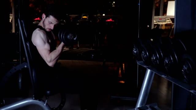 ein fitter mann, der hantel im fitnessstudio trainiert - bizeps stock-videos und b-roll-filmmaterial