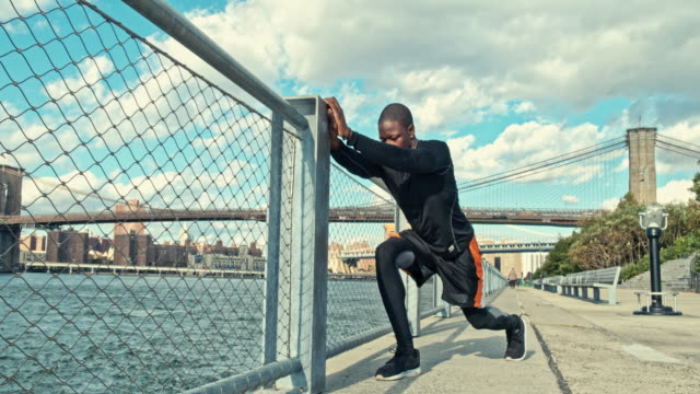 Fit man stretching arms on promenade by East River, New York