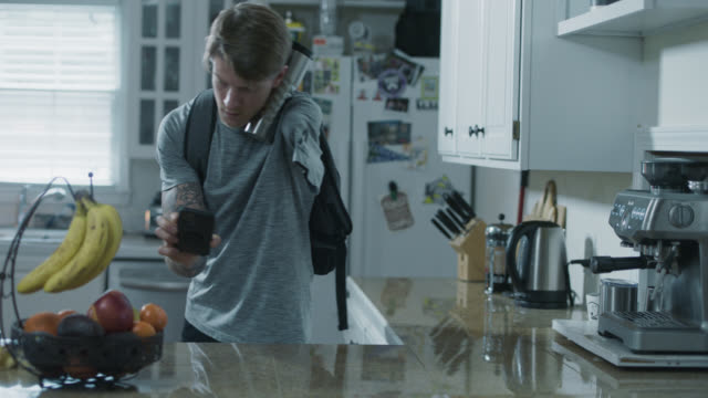 fit one armed man swiftly packs up his belongings as he checks his phone - reusable stock videos & royalty-free footage