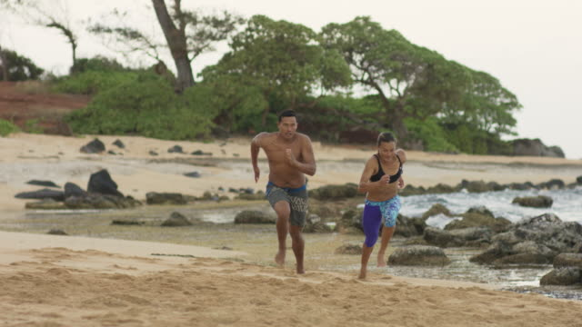 fit pacific islander man and woman racing up the beach - pacific islander stock videos & royalty-free footage