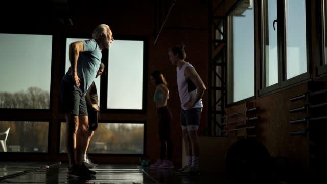 vídeos de stock e filmes b-roll de fit people warming up for training - jovem de espírito