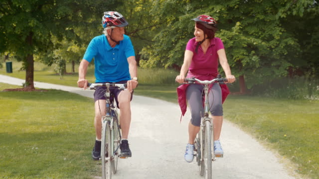 TS Fit senior couple riding bikes through the park