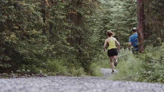 UHD 4K: älteres Paar zusammen auf einem Pfad durch den Wald laufen Fit
