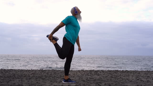 vídeos de stock e filmes b-roll de fit senior man stretching by the sea - esticar
