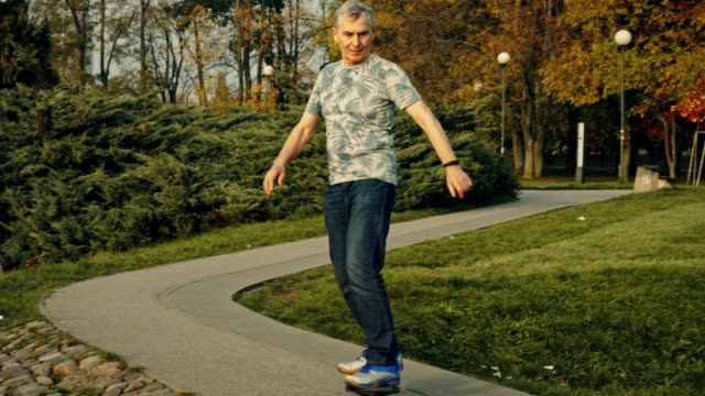 fit senior riding skateboard in park. retirement activities - sporting term stock videos & royalty-free footage