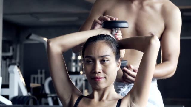 vídeos y material grabado en eventos de stock de fit sport mujer ejercicios con mancuernas con el entrenador en el gimnasio oscuro - mejora personal