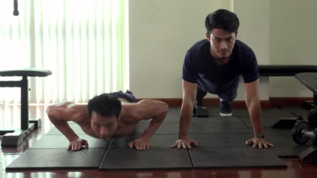 fit sporty man does push up on floor in gym - male friendship stock videos & royalty-free footage