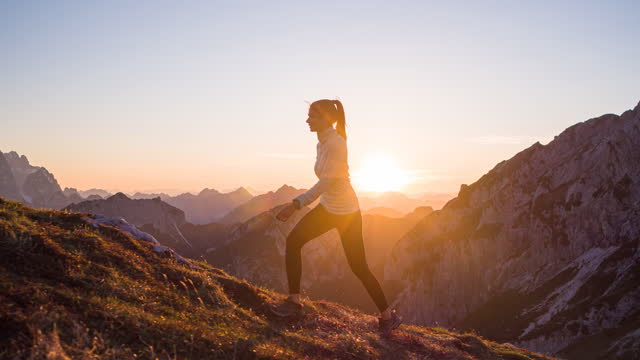 vídeos de stock e filmes b-roll de fit woman athlete maintaining a healthy lifestyle, hiking in mountains over rocky trails and grassy slopes at sunset - estilo de vida ativo