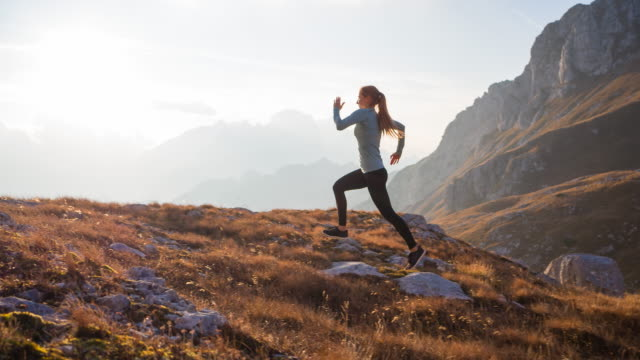 fit woman athlete maintaining a healthy lifestyle, running in mountains over rocky trails and grassy slopes at sunset - brightly lit video stock e b–roll