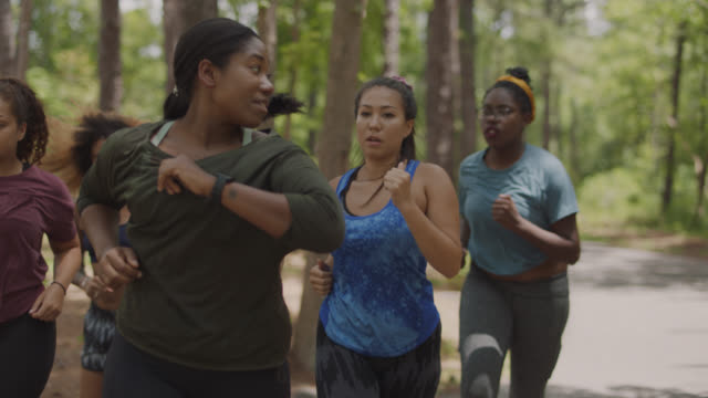 slow mo. cu. fit woman checks her smart watch while running with a group of athletic women on a path in the forest - smartwatch video stock e b–roll
