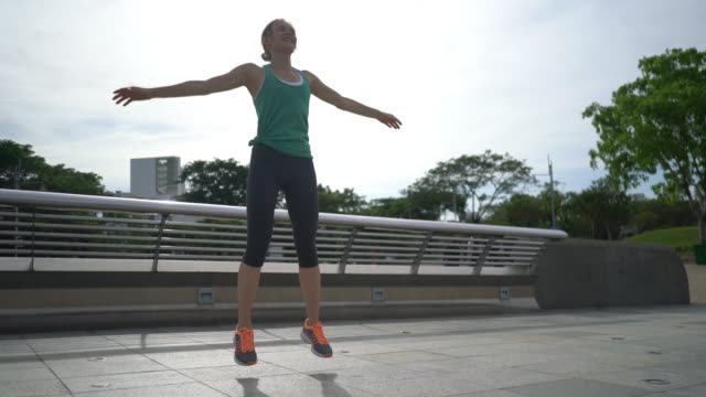 fit woman doing jumping jacks - star jump stock videos & royalty-free footage