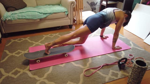 vídeos y material grabado en eventos de stock de mujer en forma haciendo ejercicio en la sala de estar usando un monopatín - entrenamiento sin material