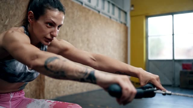 fit woman exercising on rowing machine - weight training stock videos & royalty-free footage