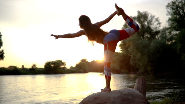 Fit woman in leggings doing yoga by the river