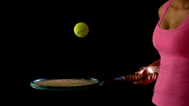 fit woman in pink bouncing a tennis ball on racket - tennis ball stock videos & royalty-free footage