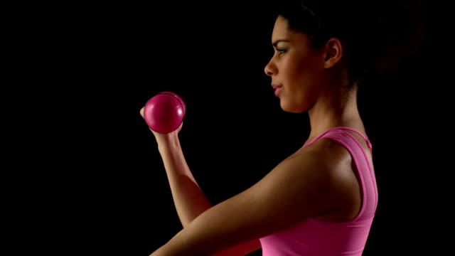 vidéos et rushes de fit femme exercice avec haltères en rose - poids pour la musculation