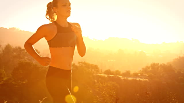 vidéos et rushes de femme en bonne forme piste de faire du jogging de los angeles en slow-motion - hollywood california