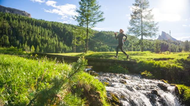 Fit Woman Joggen auf einer grünen Wiese, über eine Brücke über Bach