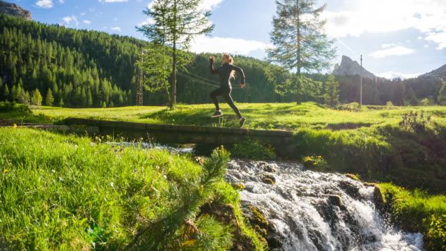 vídeos y material grabado en eventos de stock de fit mujer corriendo en un prado verde hierba, a través de un puente sobre el arroyo - corredora de footing