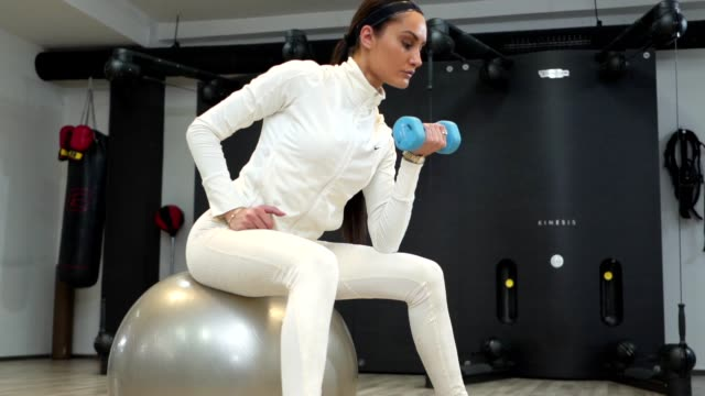 fit woman lifting dumbbell while sitting on a fitness ball - fitness ball stock videos & royalty-free footage