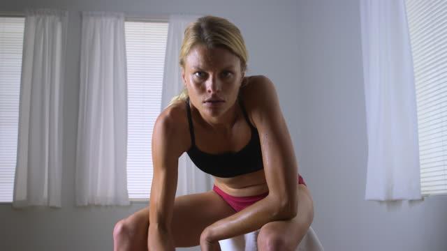 vidéos et rushes de fit woman lifting weights - cadrage aux genoux