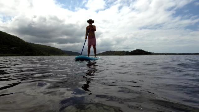 stockvideo's en b-roll-footage met fit vrouw op een stand up paddle board - peddel