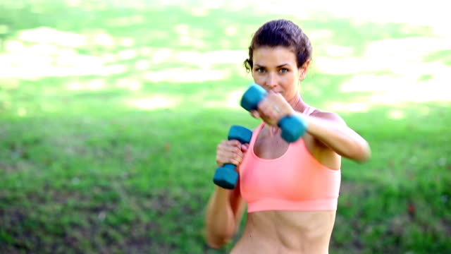 Fit woman punching with dumbbells in the park