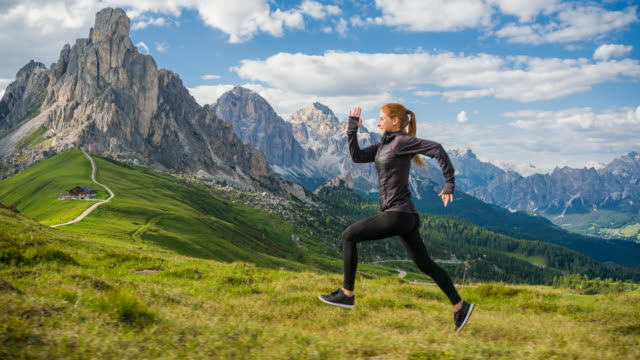 fit woman runner jogging on trails in mountain terrain in dolomites, italy - cortina stock videos & royalty-free footage