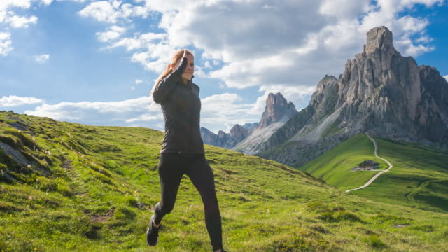 Fit woman running down a grassy trail on a meadow in mountain terrain