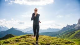 Fit woman running downhill on a meadow with mountains in background on a sunny day
