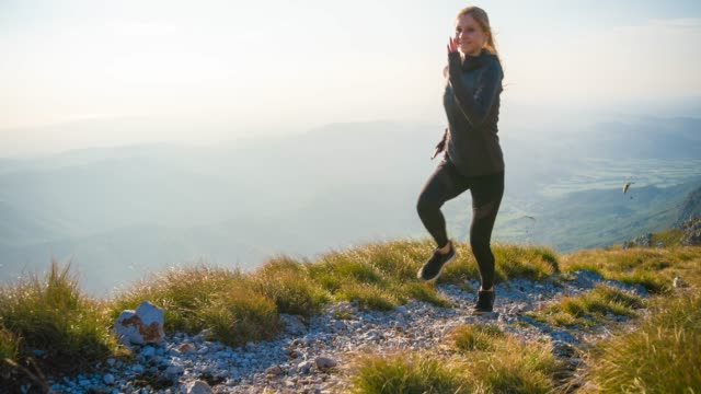 fit woman running in mountain terrain, paragliders in background - gliding stock videos and b-roll footage